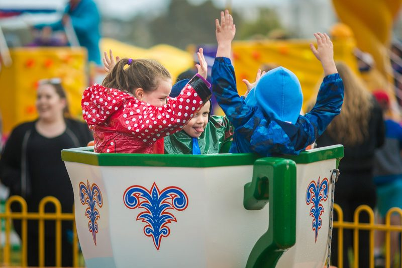 Kids with hands up on Tea Cup ride